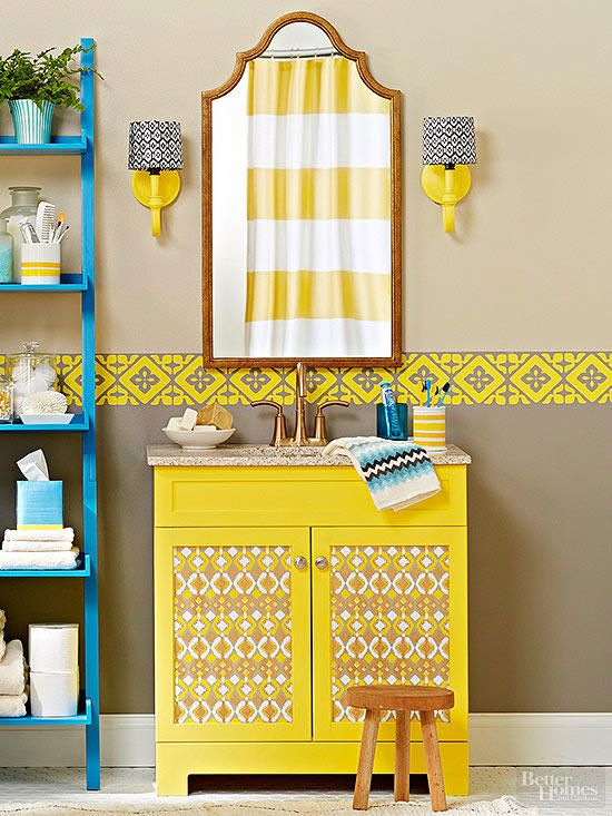 bathroom with beige color, blue shelves, yellow lining on the wall, mirror, yellow cabinet with ikat pattern on the door, yellow sconces