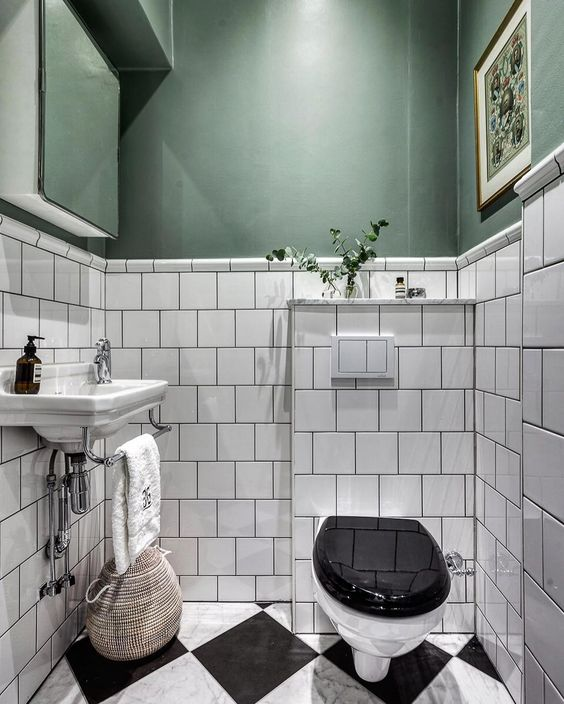 bathroom with black and white floor tiles, white square tiles, deep sage green wall, white sink, white black toilet