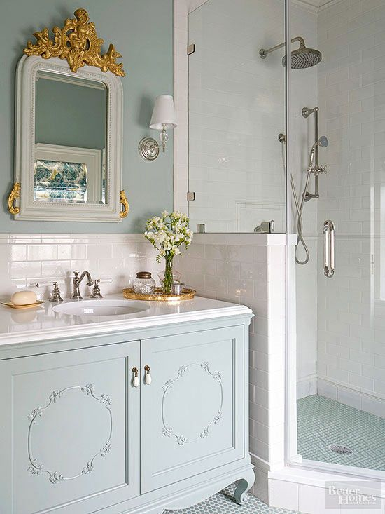 bathroom with blue cabinet, blue small tiles, white tiles wall and backsplash, white sink, white framed mirror, blue painted wall