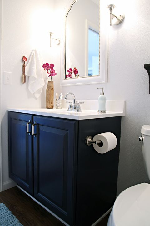 bathroom with blue cabinet with white top, sink, white framed wall mirror, white sconces, wooden floor, light blue mat, white toilet