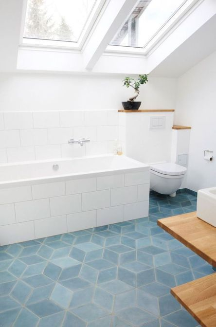 bathroom with blue hexagon tiles, white walls, ceiling with large windows, white tiles on the wall and tub, white toilet, wooden vanity with white sink