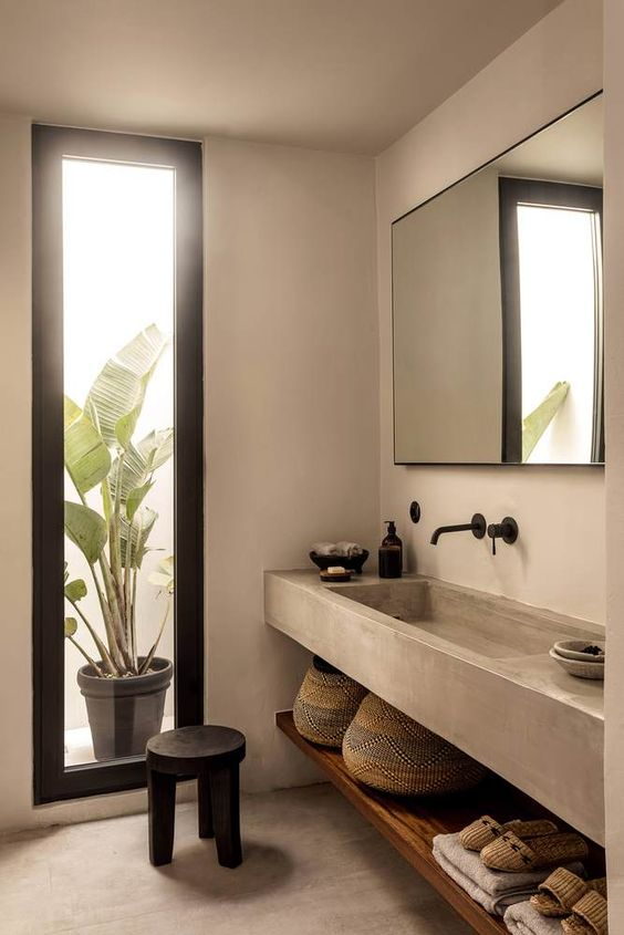 bathroom with brown concrete floor, wall, sink vanity, wooden shelf under, mirror, tall window