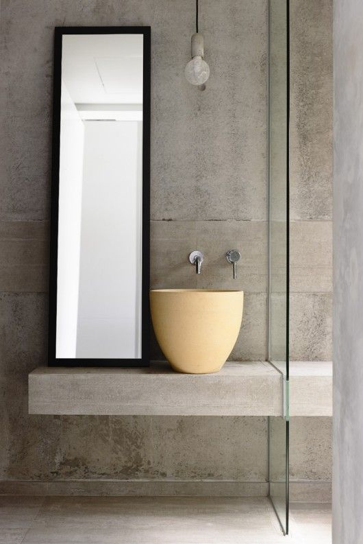 bathroom with concrete floor, wall, and vanity with yellow bowl high sink, mirror, lamp
