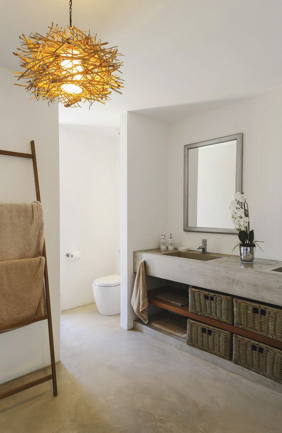 bathroom with concrete floor, white walls, concrete sink vanity, open shelves under, baskets, wooden rack, golden chandelier