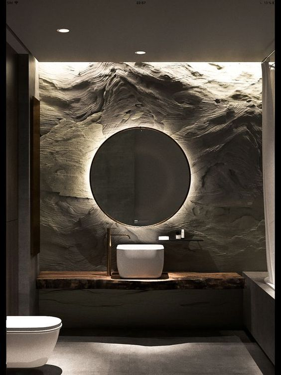 bathroom with grey floor, wooden vanity white sink, round mirror, lamp behid, textured wall, white toilet
