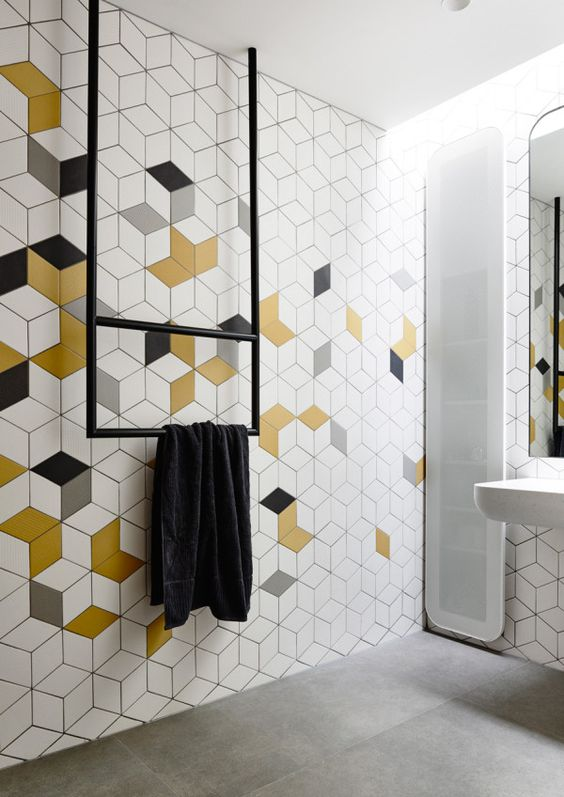 bathroom with grey flooring, white and colored hexagon with cubes pattern on the awll, white sink, long mirror, long cupboards, black rail