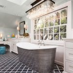Bathroom With Grey Wall, Long Chandelier, White Cabinet With White Top, White Table, Grey Tub, Dark Grey Arabesque Tiles