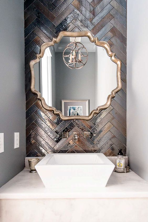 bathroom with grey wall, white marmered table top, white sink, golden framed mirror, golden chandelier, golden weave tiles