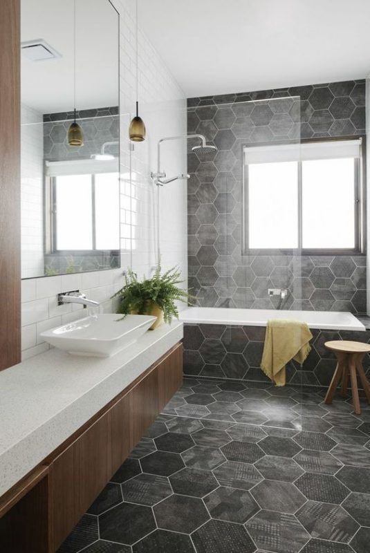 bathroom with hexagonal grey tiles on teh wall, floor, and tub with white inside, white vanity top, wooden cabinet, large mirror