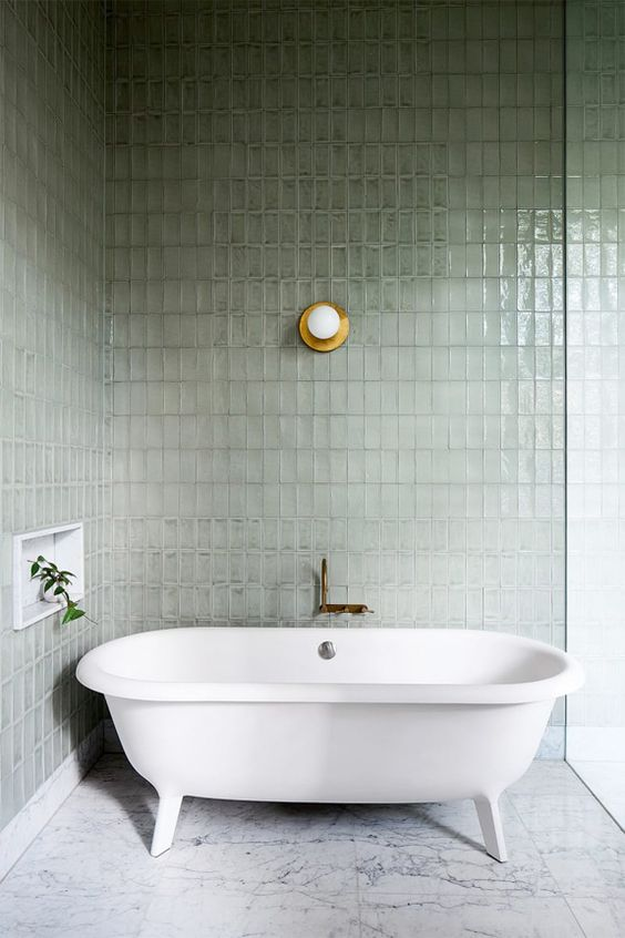 bathroom with marble floor tiles, sage greeen wall tiles, white tub