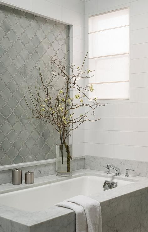 bathroom with marble tub with white inside, arabesque tiles on accnet around white subway tiles
