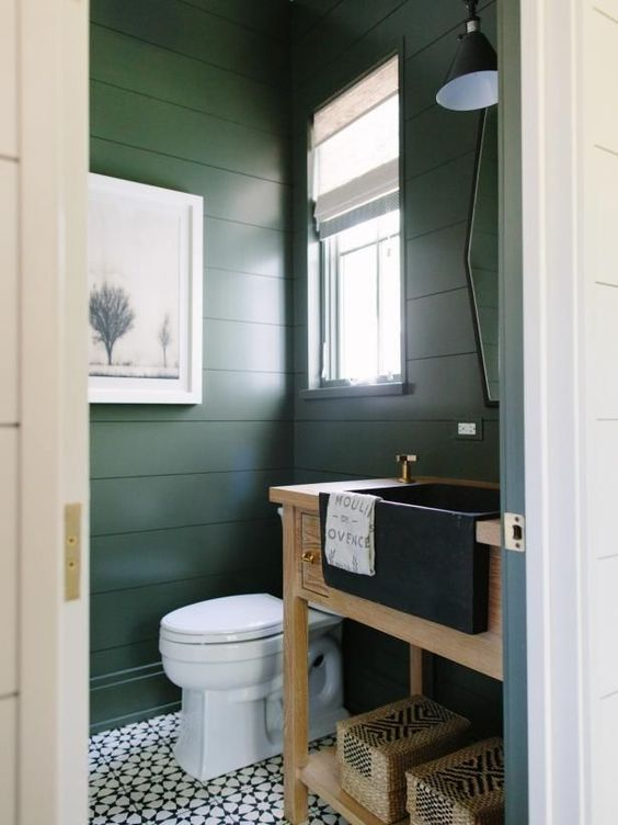 bathroom with patterned floor tiles, white toilet, sage green wood planks on the wall, wooden shelves and sink