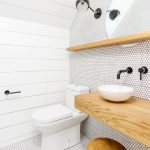 Bathroom With Tiny White Hexagon Tiles Floor Tiles, White Wood Planks Wall, Wooden Shelves With Mirror On The Back, Wooden Vanity With White Sink, Wooden Stool