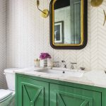 Bathroom With Walls With Wallpaper, Black Gold Framed Wall Mirror, Golden Sconces, Green Cabinet With White Marble Top Sink, White Toilet, Wooden Floor