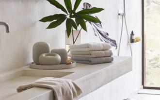 bathroom with white floor, white wall, white concrete sink vanity, plants, stool