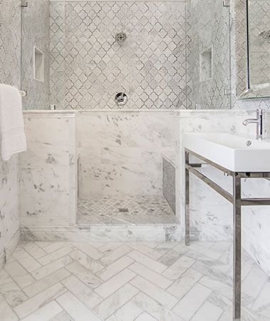 bathroom with white herringbone pattern tiles, marmer on the bottom wall, kasbah on the top wall, small tiles on the shower,