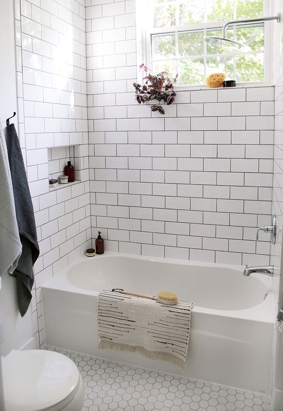 bathroom with white hexagon tiles floor, white tile on the wall, white toilet, white bathtub, silver faucet and shower