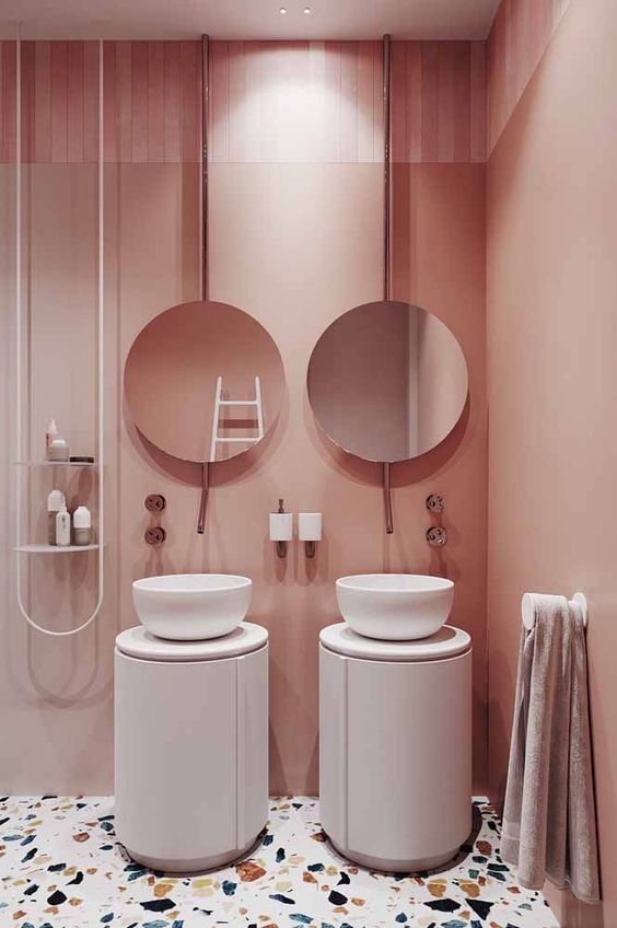bathroom with white terrazzo floor, white round cabinets, white round sink, rose pink wall, white rail shelves, frameless mirrors
