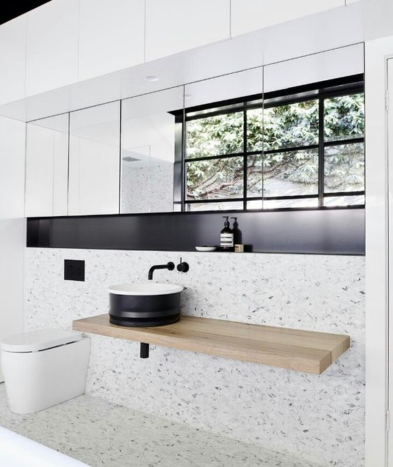 bathroom with white terrazzo on floor and wall, woodne floating vanity with black round sink, built in shelves, mirror storage