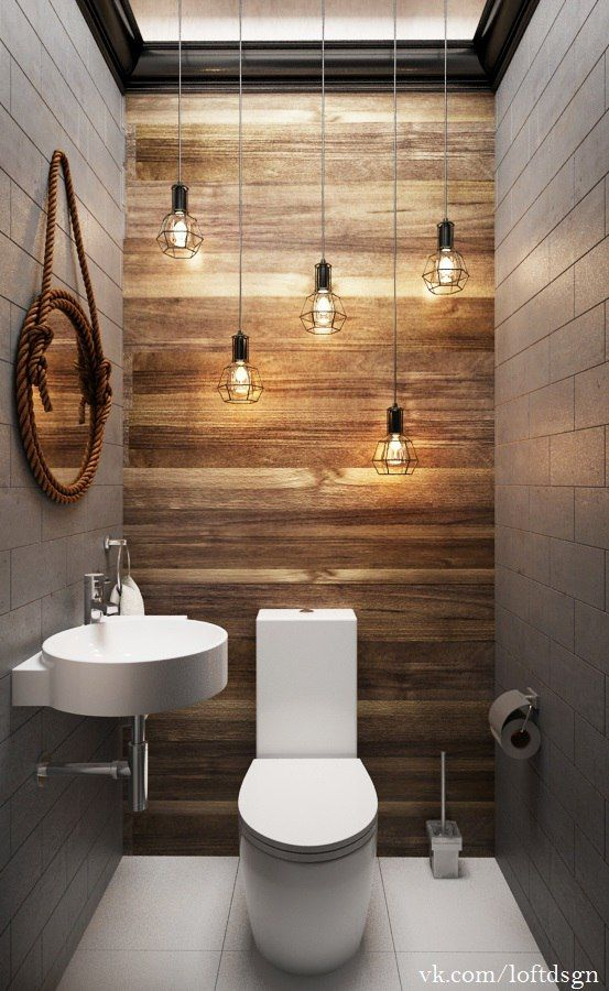 bathroom with white tile wall, wooden accent wall, white toilet, white sink, round mirror, lighting fixtures, white tiles