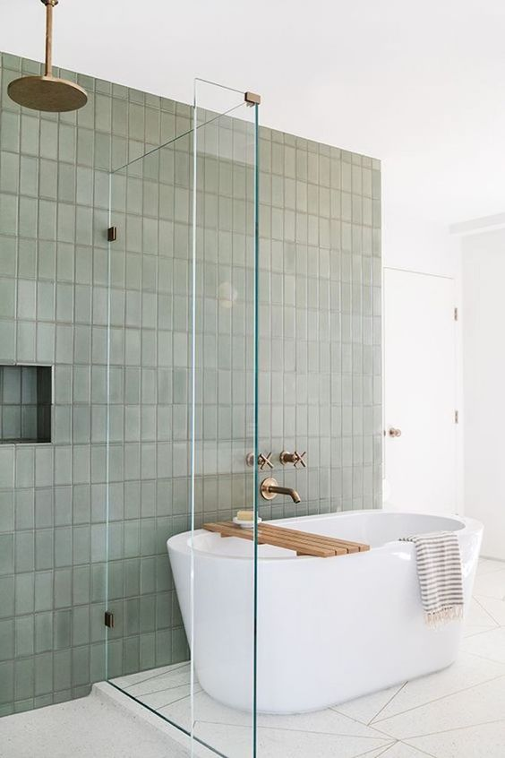 bathroom with white tiles, white tub, white wall, sage green tiles on the wall on the tub and shower area