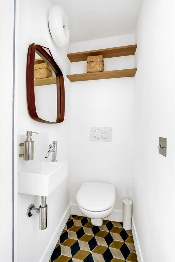 bathroom with white wall and ceiling, white toilet, wooden shelves, white small sink, yellow blue geomteric tiles