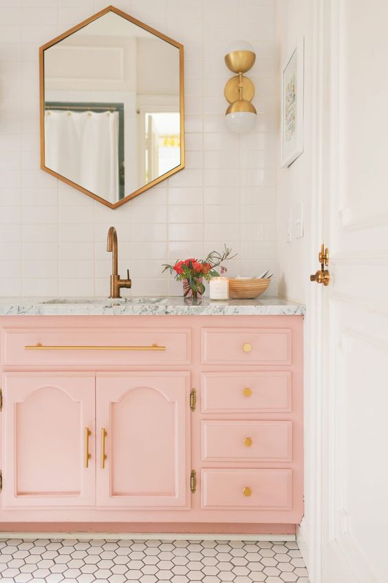 bathroom with white wall, white hexagonal small tiles floor, pink cabinet, golden framed wall mirror, grey marble top with sink, golden faucet, golden sconces