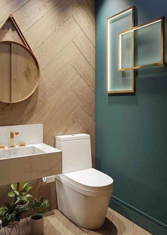 bathroom with wooden wall and floor, turquiose wall accent with golden frames decoration, white toilet, white sink, plants, mirror