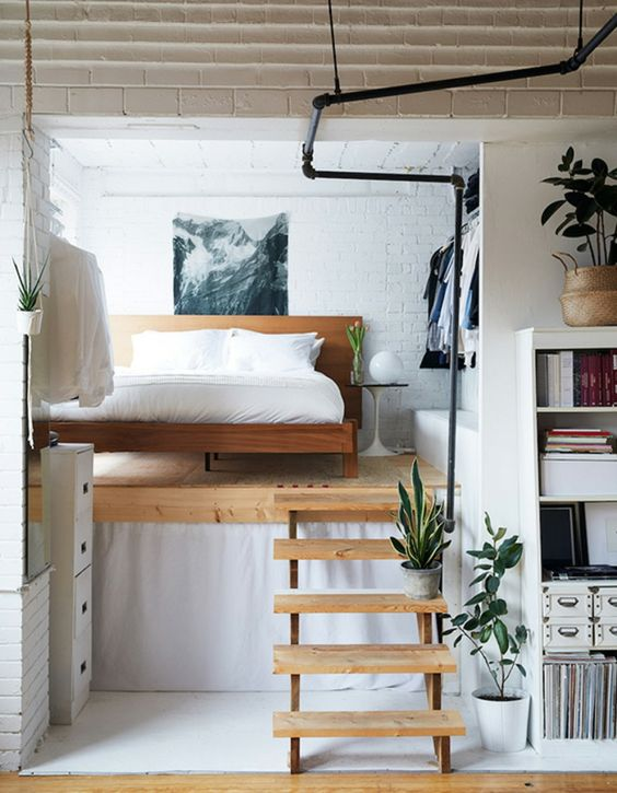bed in upper level with wooden floor, wooden stairs, white open brick, white ceiling, bookshelves, open clothes storage
