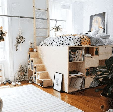 bed on the upper leve, bookshelves under, stairs   shelves, wooden floor, rug