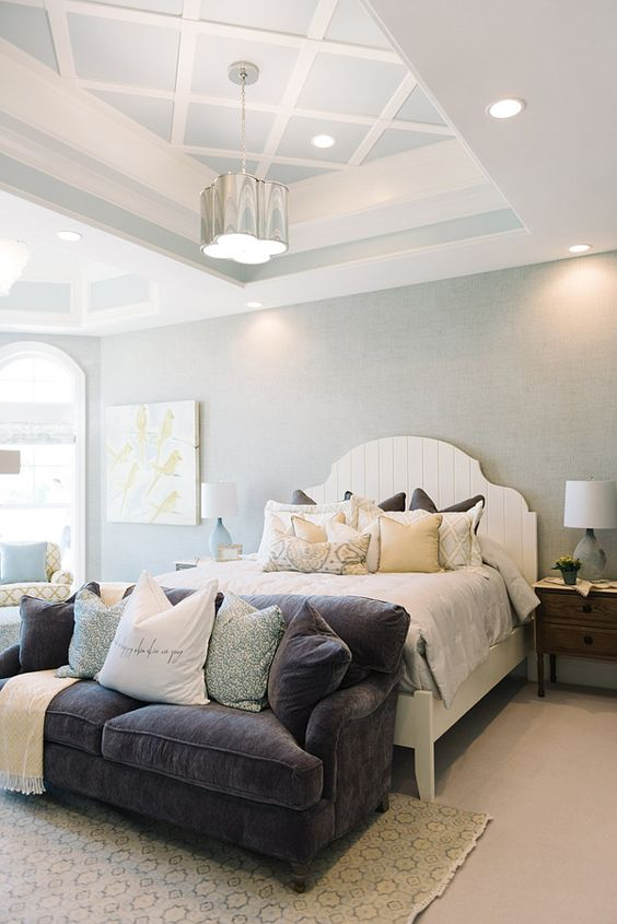 bedroom, light brown flooring, rug, white bed platform, light blue wall, white ceiling with coffered tray in light blue, pendant, grey sofa
