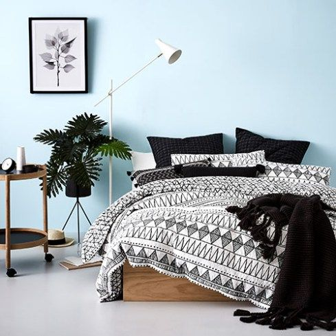 bedroom, white floor, light blue wall, wooden bed platform, black and white tribal bedding, side table, white floor lamp