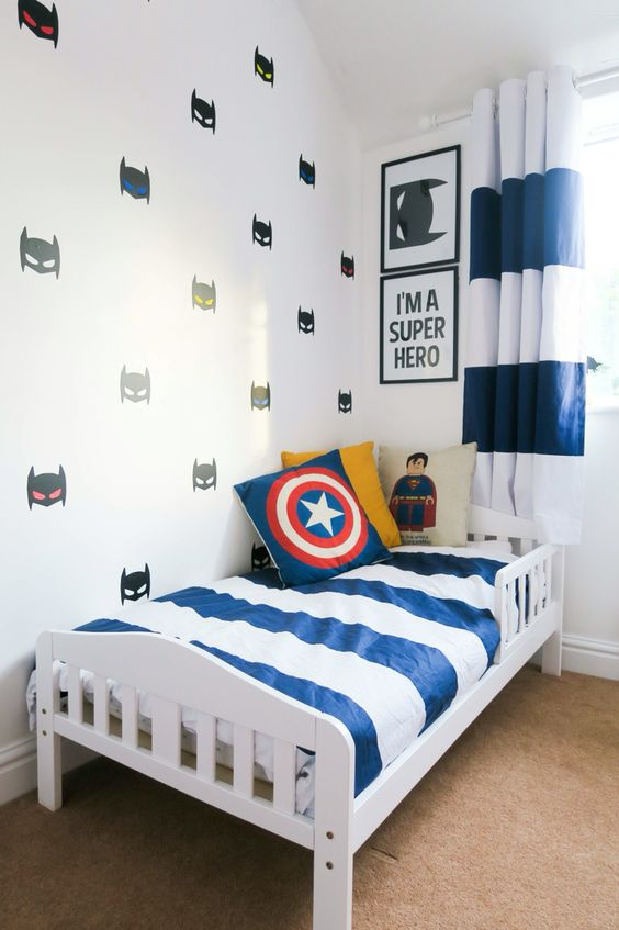 bedroom with brown rug, white bed, striped linen, captain america, superman pillows, batman wallpaper