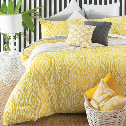 bedroom with rug, white table lamp, white basket with pillows, bed with yellow ikat pattern bedding
