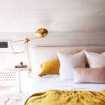 Bedroom With White Round Night Stand, Golden Table Lamp, White Wooden Walls, White Bedding, Yellow Blanket, Yellow, Pink, White Pillows, Pink Headboard Bed