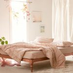 Bedroom With Wooden Floor, Pink Rug, White Curtain, Windows, Flowers, Plants, Paintings