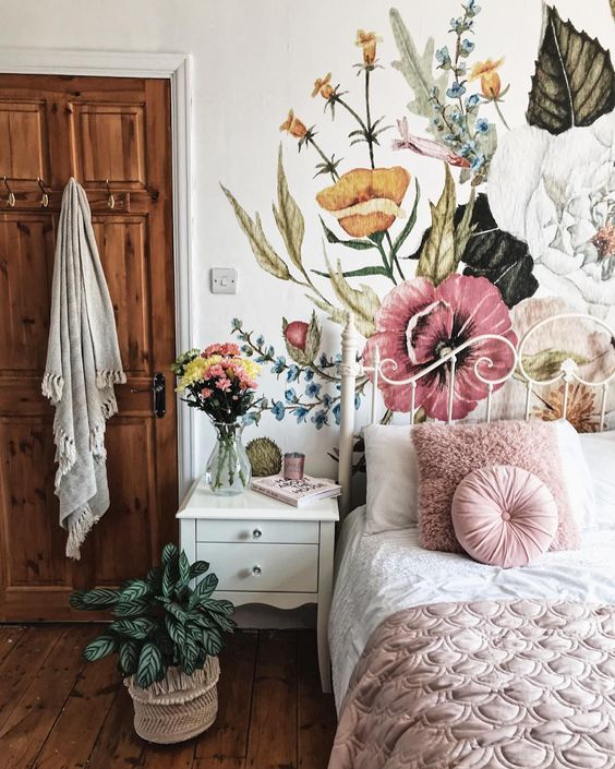 bedroom with wooden floor, white metal platform with white pink bed, white side table cabinet, flower wallpaper with white bakground
