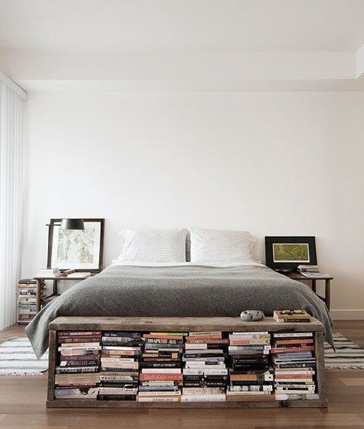 bedroom with wooden floor, white wall and ceiling, grey bed, bookshelves near the nightstands, under the bench