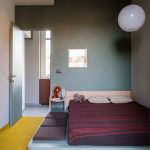 Bedroom, Yellow Floor, Blue Bed Platform, Purple Seating Pillow, Grey Wall, White Globe Pendant