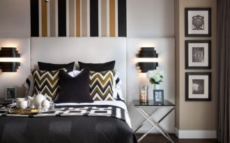 bedroomw ith dark wooden floor, rug, white platform bed with dark bedding, white wall with stripes on accent wall and ceiling continued, sconces