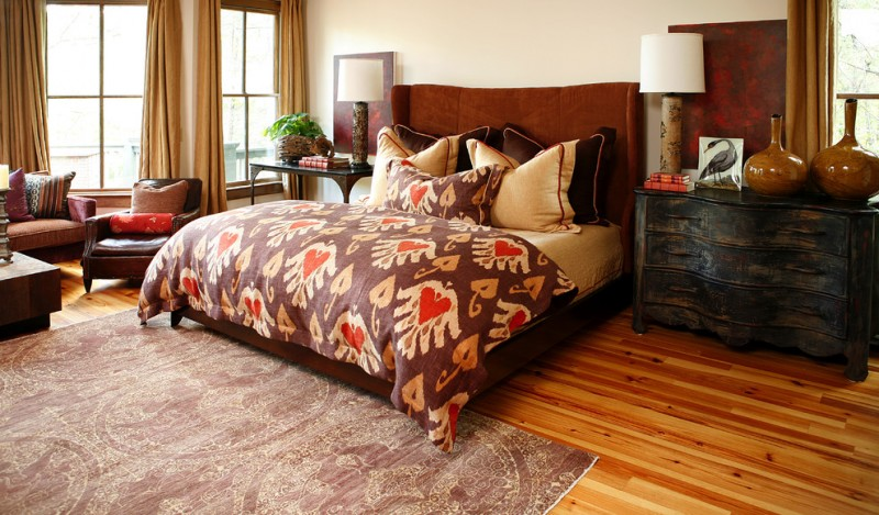 bedside table height wooden flooring area rug brown bedding velvet brown headboard black dresser black table windows table lamps pillows