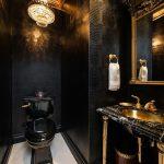 Black Bathroom With Beige Tiles Floor, Black Textured Tiles On Wall, Black Toilet, Black Marble Sink With Golden Legs, Golden Framed Mirror, Golden Chandelier, Statement Ceiling