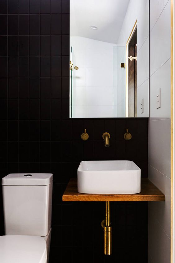black bathroom with black tiles wall, white tiles wall, white toilet, white sink on wooden vanity