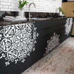 Black Kitchen Cabinet With White Tribal Pattern, White Open Brick Wall, Black Marble Top, Wooden Floor
