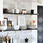 Black Wooden Open Shelving With Golden Support On White Tiles Wall