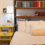 Brown Wooden Bookcase Behind Headboard Bed, White Linen Bed, Yellow Nightstands, White Table Lamp