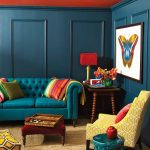 Chesterfield Sofa In Teal With Tufted Back In A Living Room With Teal Orange Wall, Wooden Side Table, Yellow Chair, Yellow Ottoman