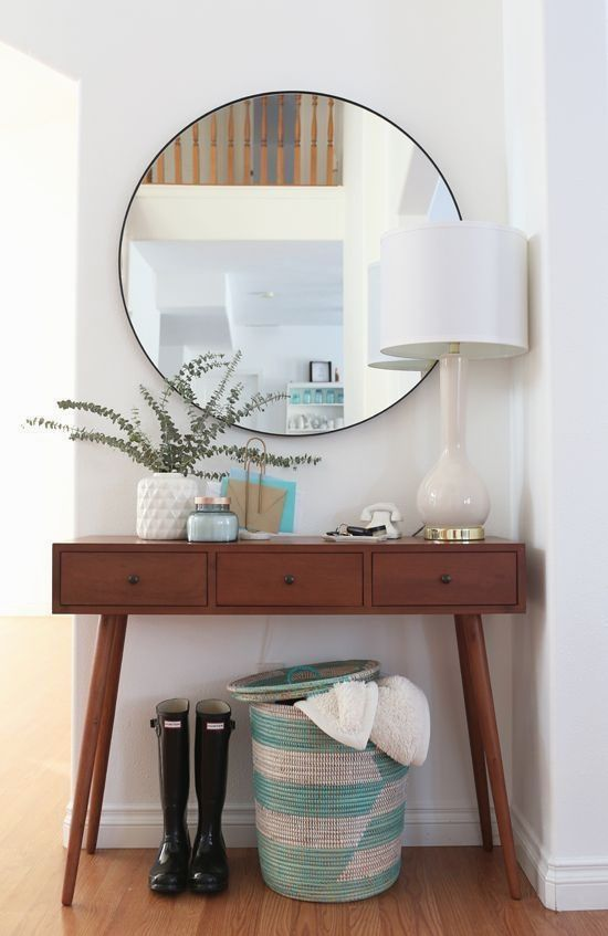 classic wooden console table with three drawers, four feet, white table lamp and white case on top, round mirror, basket