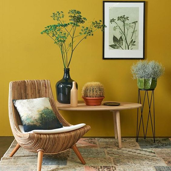 corner, rug, rattan curvy chair, mustard wall, wooden coffee table, plants