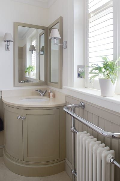 corner vanity with round finish to the front, cream marmer top, beige cabinet following, two mirrors following the wall